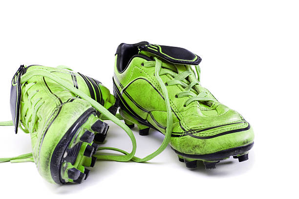 Soccer cleats Green soccer cleats isolated on white background. studded stock pictures, royalty-free photos & images