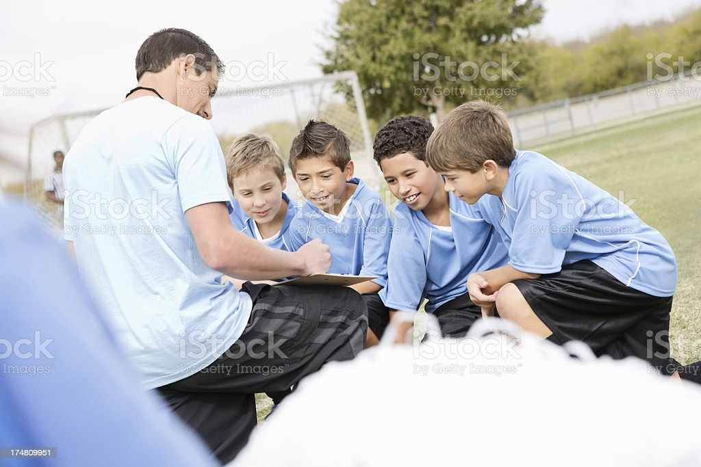Soccer coach explaining play to kids team during game royalty-free stock photo