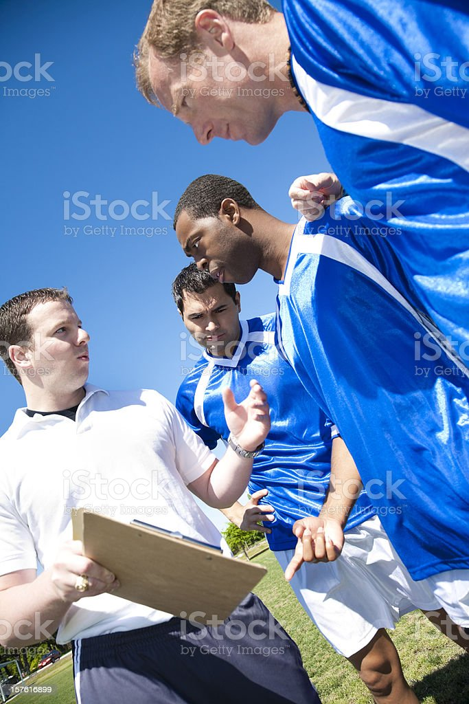 Soccer Coach Explaining Strategy to Players royalty-free stock photo
