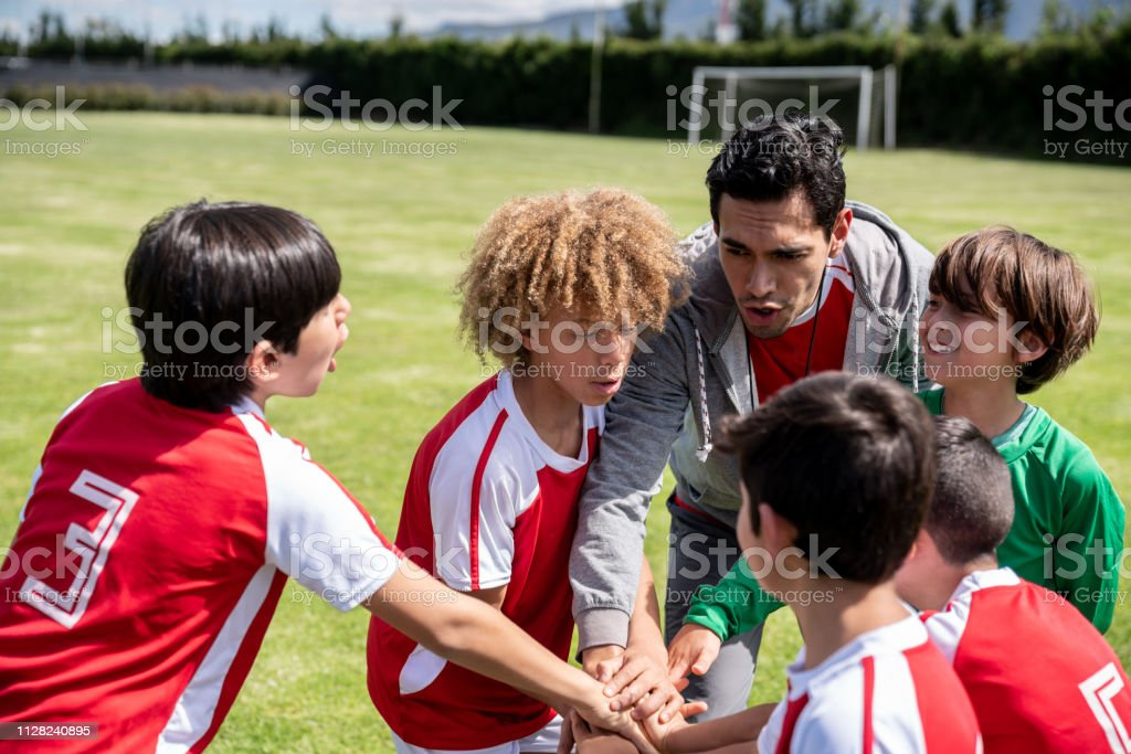 Soccer coach having a pep talk with a group of young players and...