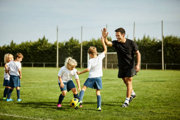 Fußballtrainer high-fiving mit Jungen während des Trainings – Foto