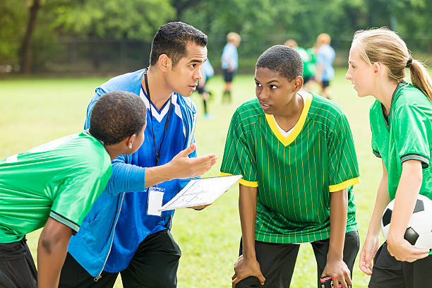 soccer coach talks about play during time out - coach stock photos and pictures