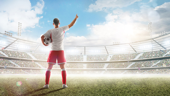 Soccer concept. Soccer player holds a soccer ball on the professional stadium and talking to fans. View from behind. Sport. Sunny day
