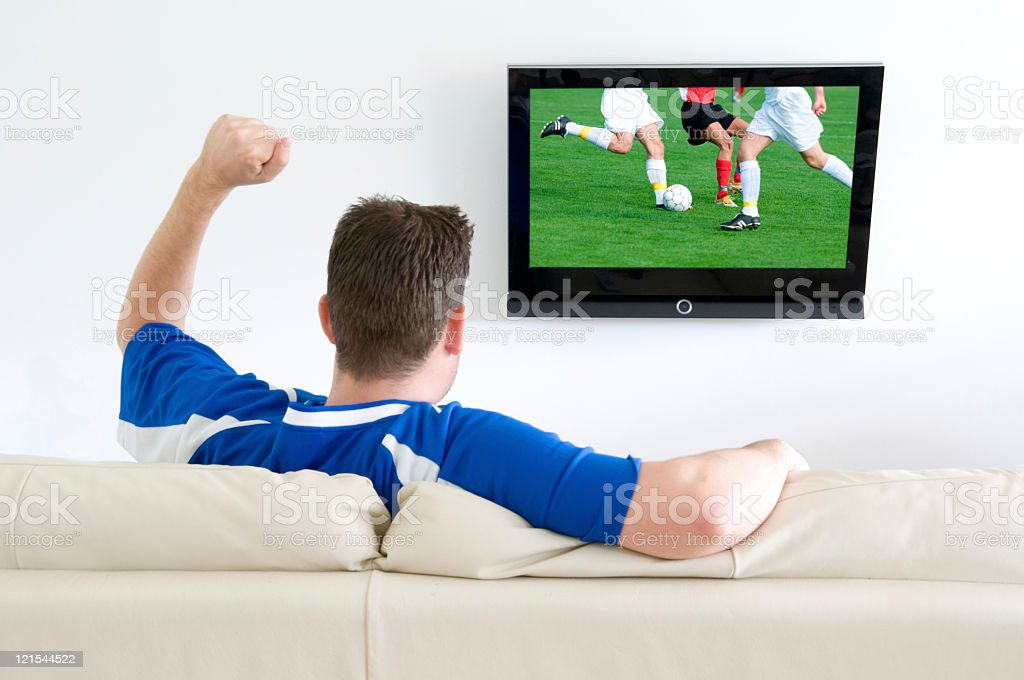 Soccer fan cheers while watching a football match on tv royalty-free stock photo