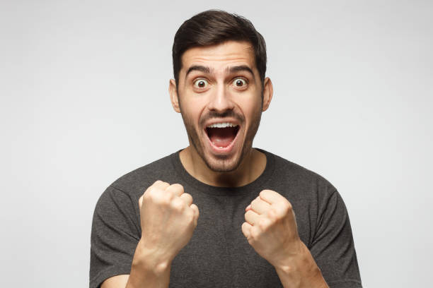 soccer fan concept. young attractive man shouting while his team win, raised both fist in victory gesture, isolated on gray background - soccer supporter portrait imagens e fotografias de stock