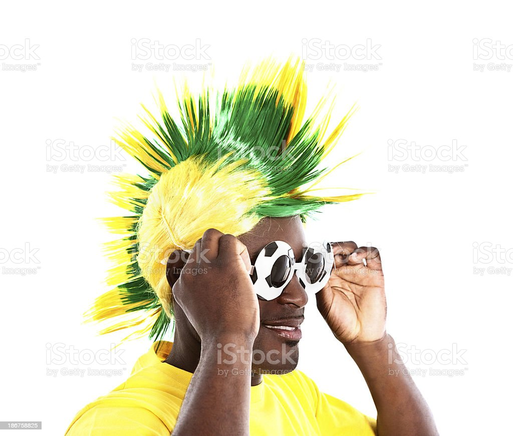 Soccer fan in Brazilian team colors tries on funky sunglasses royalty-free stock photo