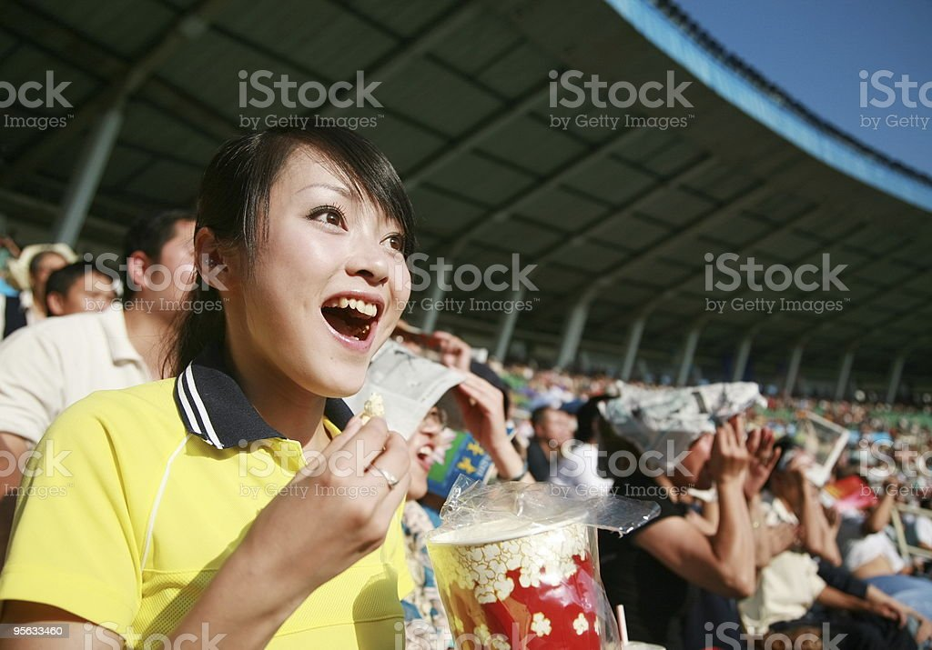 A soccer fan screaming for her team while holding a popcorn  royalty-free stock photo