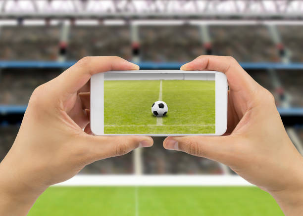 Soccer fan taking pictures of a ball on the grass stock photo