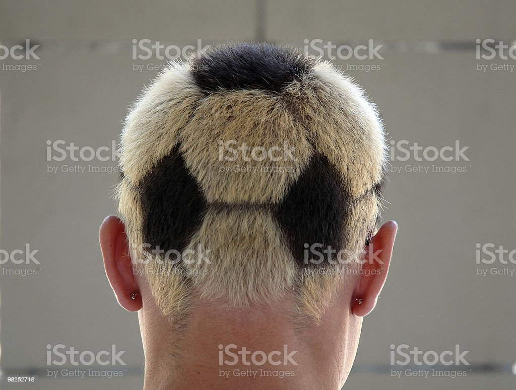 Soccer fan with unique soccer ball haircut stock photo