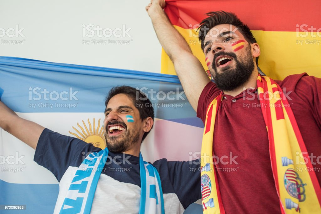 Soccer fans cheering for national teams at the game stock photo