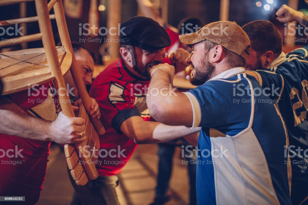 Soccer fans fighting in bar stock photo