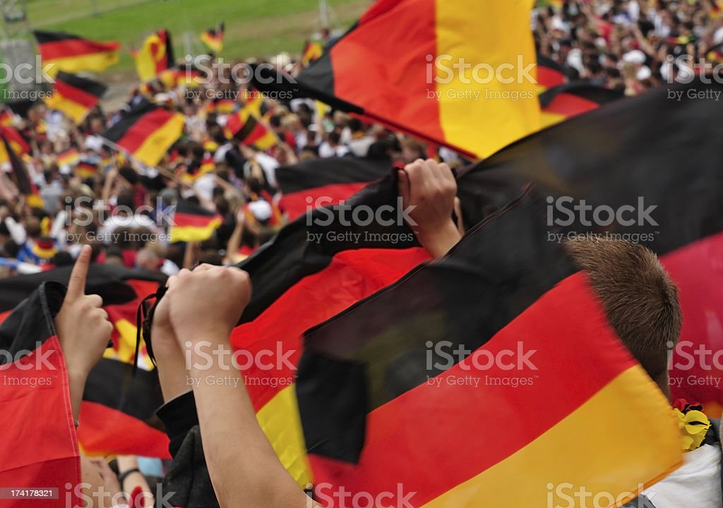 Soccer fans in a stadium waving German flags. stock photo