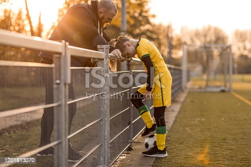 Middle Aged Redhead Father coaching soccer to his daughter at a football game on a sunny autumn day