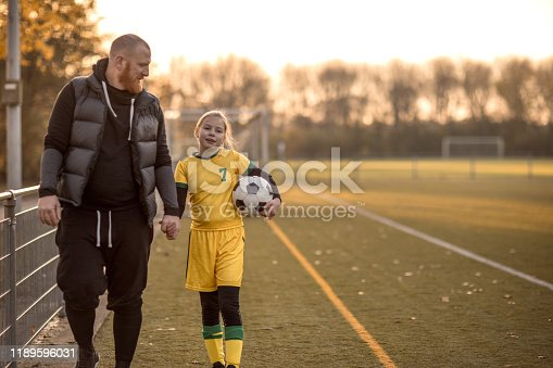 Soccer Father accompanying his daughter to football training on a summer autumn day