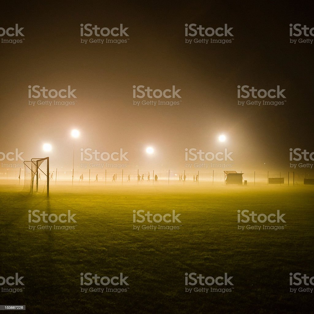 Soccer field in the fog surrounded by lights stock photo