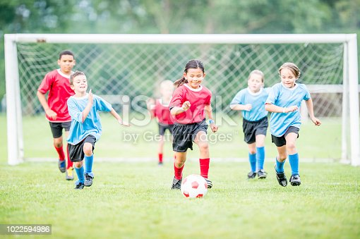 A group of elementary school students are outdoors on a warm sunny day. They are wearing their soccer uniforms. A girl in the red team is running with the ball
