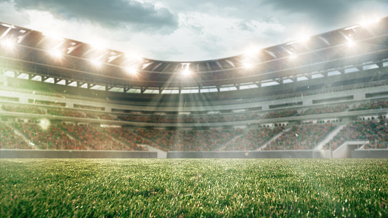 Soccer field with illumination, green grass and cloudy sky, background for design or advertising