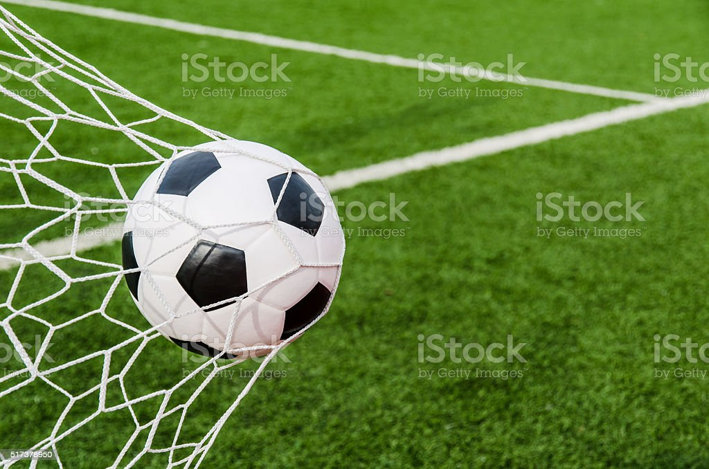 Soccer football in Goal net with green grass field. stock photo
