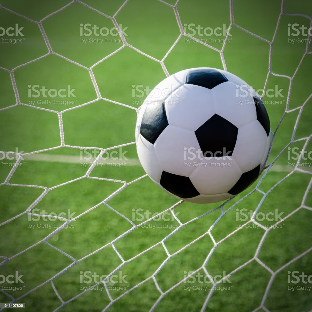 1a1022aaf Soccer football in Goal net with green grass field. - Stock image .
