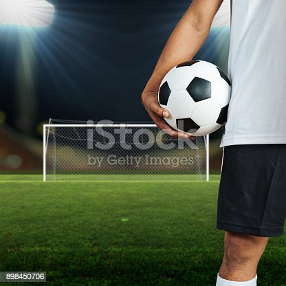 istock Soccer football player holding a ball in a football field 898450706