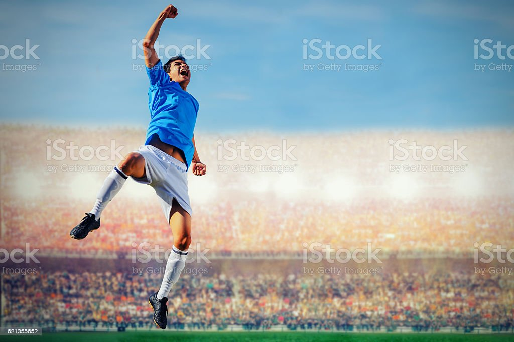 soccer football player in blue team concept celebrating goal in stock photo