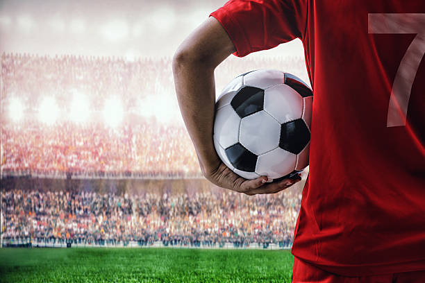 soccer football player in red team concept holding soccer ball - サッカー ストックフォトと画像