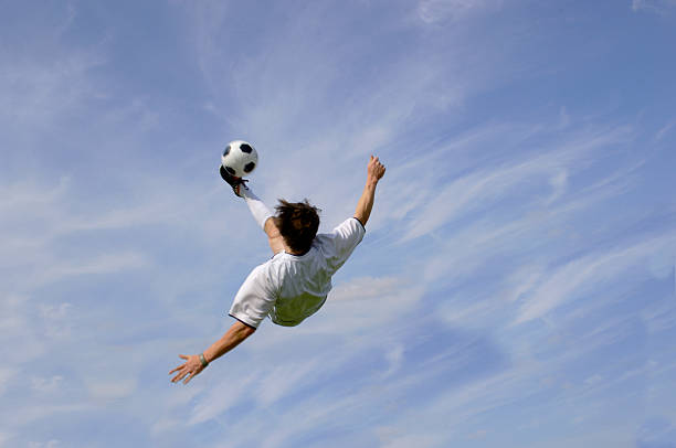 Soccer football player in the air performing bicycle kick stock photo