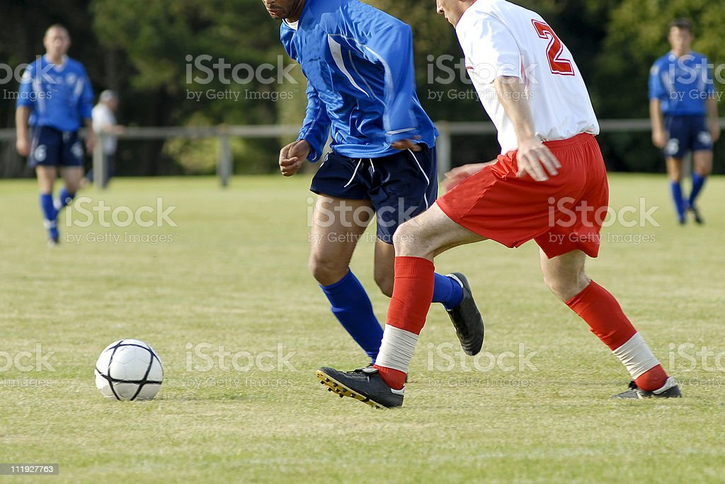 A soccer game between youths in a field royalty-free stock photo