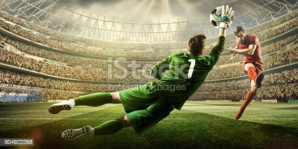 A male soccer player kicks a ball and soccer goalie jumping in motion for a ball while defending his gates on wide angle panoramic image of a outdoor soccer stadium or arena full of spectators under a sunny sky. The image has depth of field with the focus on the foreground part of the pitch. With intentional lensflares. Players are wearing unbranded soccer uniform.