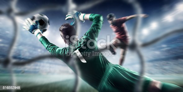 Behind the gate net view - a male soccer goalie jumping in motion for a ball while defending his gates on wide angle panoramic image of a outdoor soccer stadium or arena full of spectators under a sunny sky. The image has depth of field with the focus on the foreground part of the pitch. Players are wearing unbranded soccer uniform.
