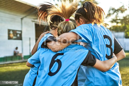 Female soccer players are huddling on sports field. Girls are celebrating success after winning match. They are in blue sportswear.