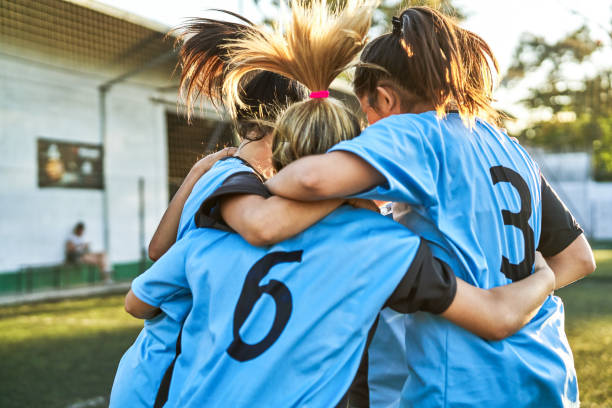 Soccer girls huddling after winning match stock photo