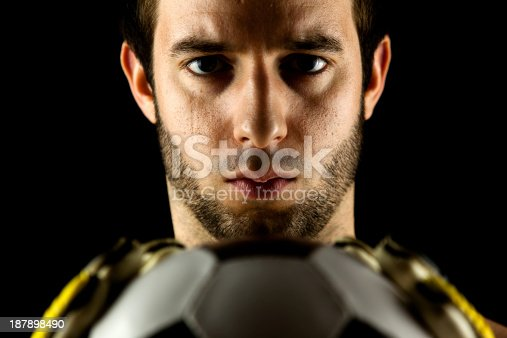 istock soccer goal keeper (player) with classic ball (low-key studio shot) 187898490