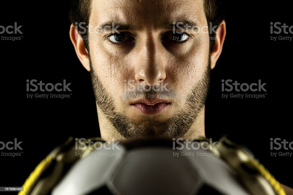 soccer goal keeper (player) with classic ball (low-key studio shot) stock photo