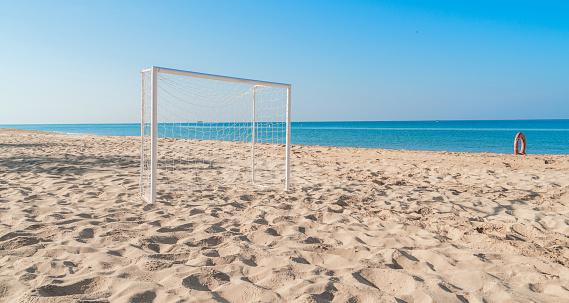 Soccer goal post on the beach with sand and blue sky
