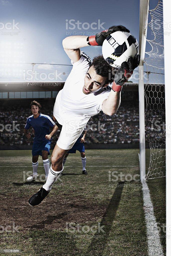 Soccer goalie catching soccer ball stock photo