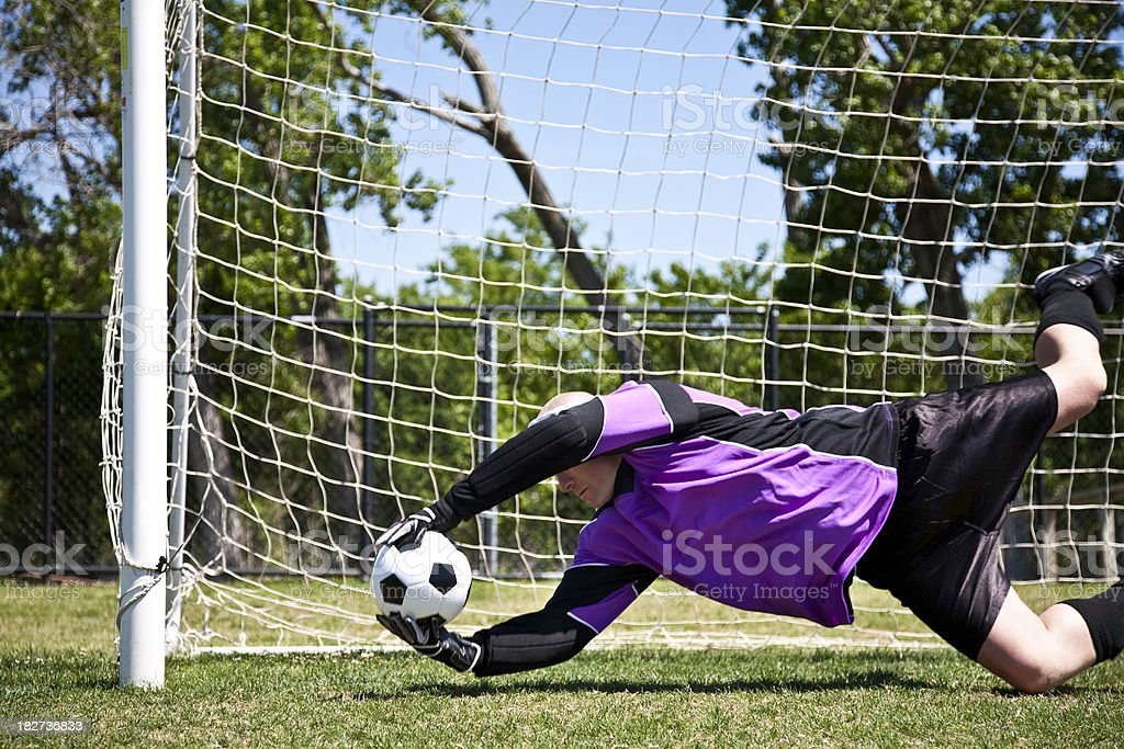 Soccer Goalie Reaching for Ball From Entering the Net royalty-free stock photo