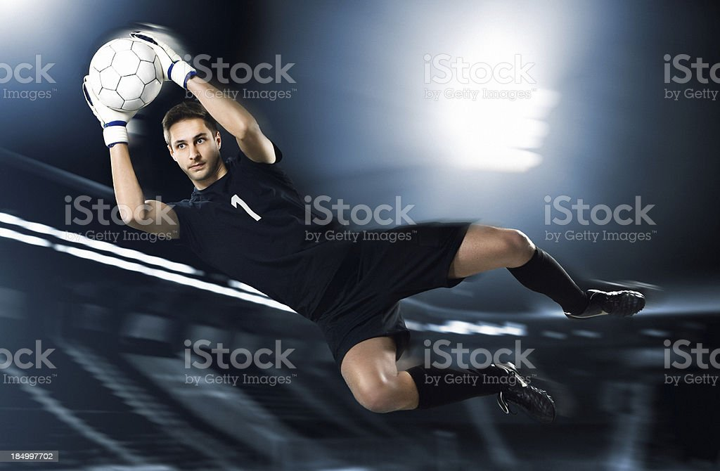 soccer goalkeeper catching ball in mid-air stock photo