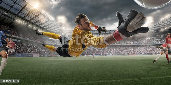 Extreme close up view from inside goal of professional soccer goalkeeper in mid air diving to save football during soccer match. The action occurs in a generic outdoor floodlit football stadium full of spectators under a stormy evening sky. All players are wearing generic unbranded kit. Stadium advertising is fake.