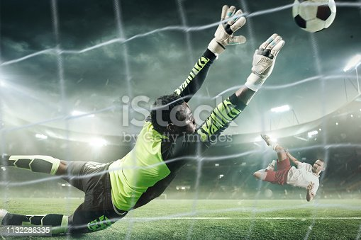 Professional soccer goalkeeper in action playing at the night stadium. Goalkeeper trying to catch the ball in flight. 3D model of the stadium was created by me (the author)