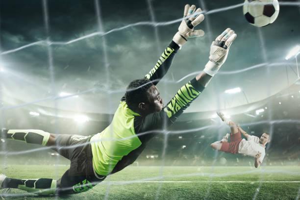 voetbaldoelman in actie op professionele stadion. - scoren stockfoto's en -beelden