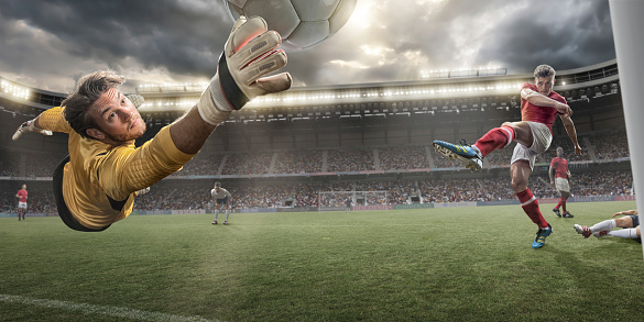 A close up image of a professional soccer goalkeeper with outstretched hand reaching to make a save from rival player who has just kicked football. Action takes place in a generic floodlit outdoor stadium under a stormy evening sky. All players are wearing generic unbranded soccer kit. With intentional lensflare.