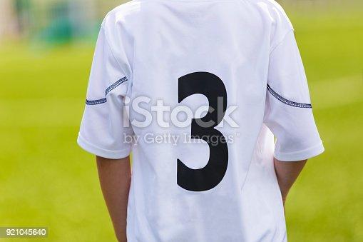 istock Soccer jersey closeup. Young sport player closeup on sport t-shirt uniform. Sport stadium in the background. 921045640