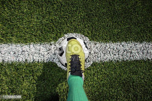 Top view of a soccer player standing on the center of soccer field