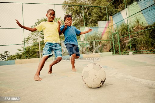 Two boys from the favelas in Rio de Janeiro challenge each other for the soccer ball on a concrete pitch.