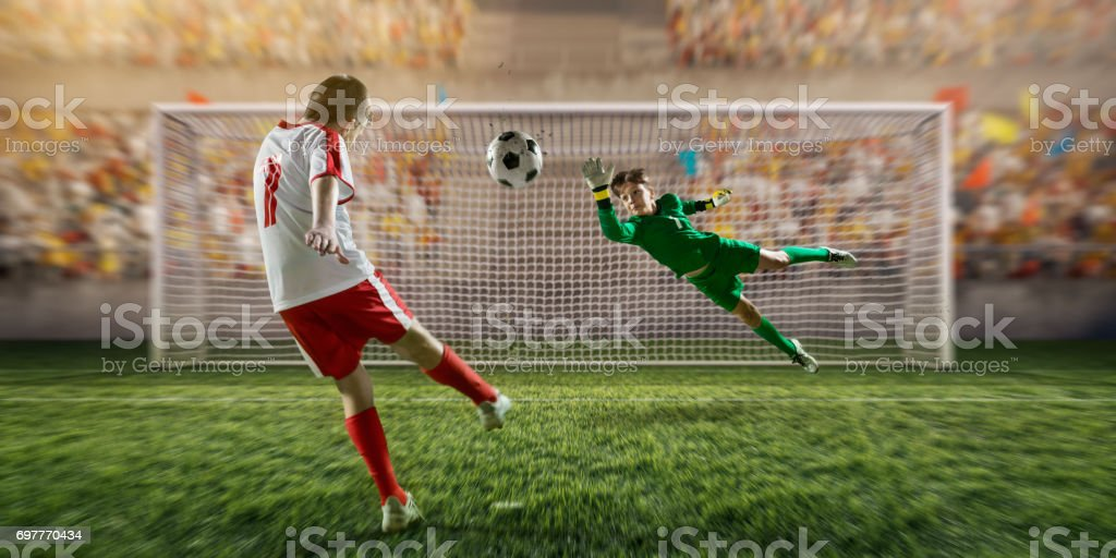 Soccer kids player scoring a goal. Goalkeeper tries to hit the ball stock photo