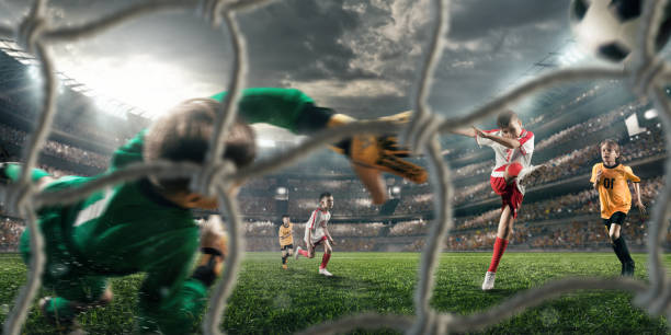 soccer kids players scoring a goal. goalkeeper tries to hit the ball - soccer competition stock photos and pictures