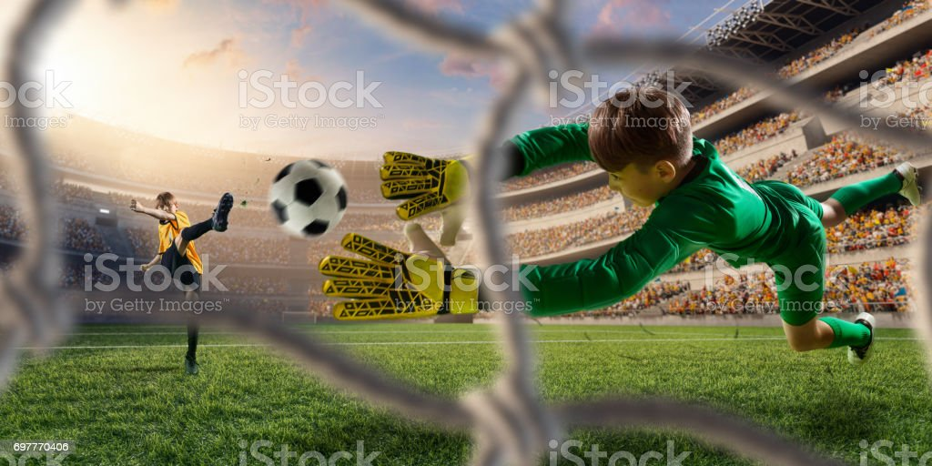 Soccer kids players scoring a goal. Goalkeeper tries to hit the ball stock photo