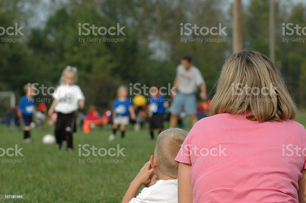 Soccer Mom and Brother Watching Sister Play Game stock photo