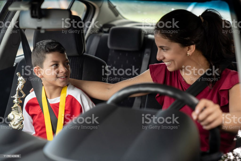 Soccer mom getting excited about her son getting a trophy and giving...